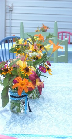 Beautiful summer flower in mason jars tied with blue ribbon adorn each table with lace table cloths.